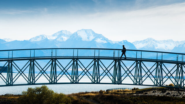 Tourist walking on the footbridge with mighty Southern Alps in the background, Lake Tekapo, South Island