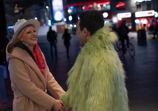 Happy stylish couple holding hands on city street at night