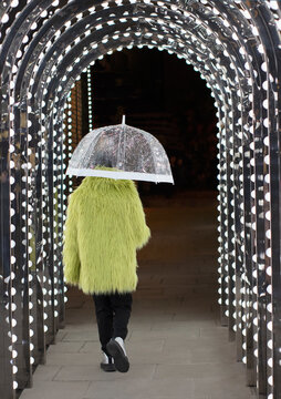 Eccentric young man in feather coat with umbrella under arch lights