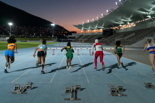 Female track and field athletes racing to hurdles on track at night