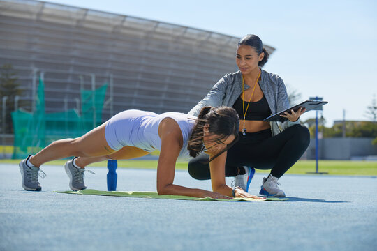 Trainer helping female track and field athlete doing planks on track