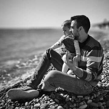 Full Length Of Man Sitting With Daughter On Pebbles At Beach