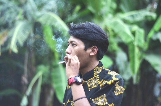 Portrait Of Young Man Smoking Cigarette Outdoors