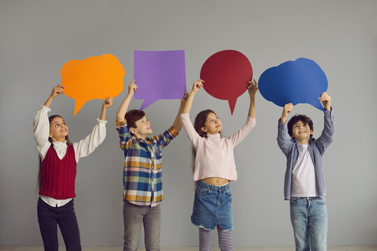 Children of new generation express opinions. Group of cute junior kids holding up multicolored clean paper bubbles. Happy smiling elementary school boys and girls with text bubbles standing in studio