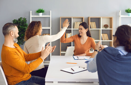 Happy professional business teams making successful deal. Group leaders celebrating success and teamwork. Two smiling women entrepreneurs high fiving each other sitting at office table in work meeting