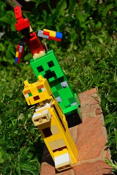 LEGO Minecraft figures of Ocelot Cat and Creeper green monster mob with parrot on his head, standing on thin ceramic tile placed in garden lawn, spring daylight sunshine.