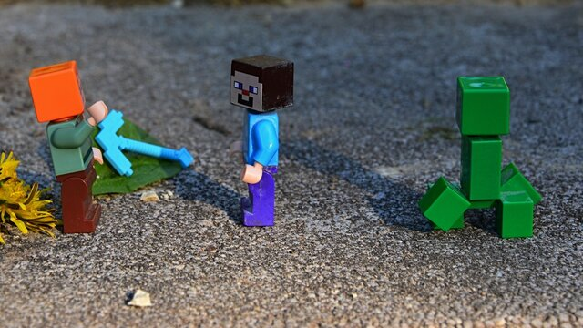 LEGO Minecraft Alex and Steve with explosive green Creeper monster mob approaching, Alex raising her hand as warning. Leaves, dandelion flower and diamond Minecraft pickaxe placed on stone ground