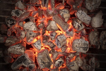 BBQ Grill Pit With Glowing And Flaming Hot Charcoal. Hot Charcoal In Barbecue Grill Pit With Flames Background Texture, Close-up. Flaming Charcoal In Grill Pit Isolated On Black Background.
