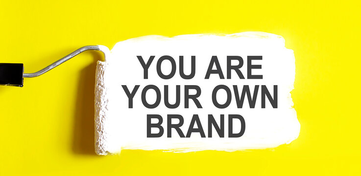 YOU ARE YOUR OWN BRAND .One open can of paint with white brush on it yellow background.