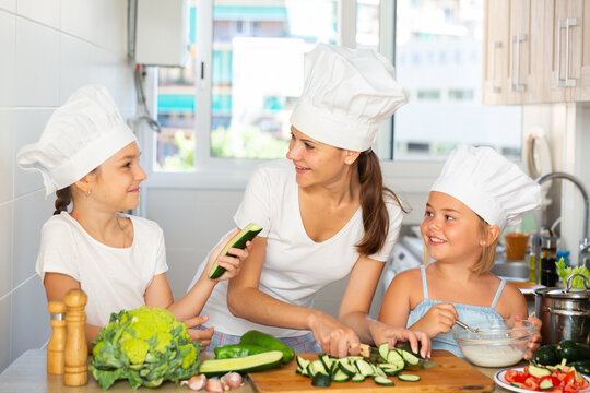 Portrait of smiling little sisters with mother in caps learning how to cook