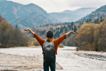 Fototapeta happy woman hiker with a backpack on the river bank look into the mountains and autumn forest nature obraz