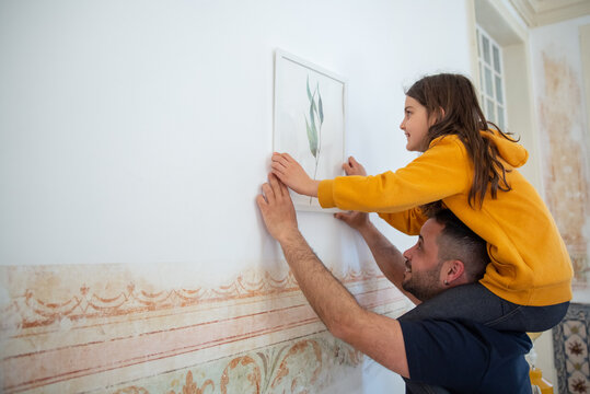 Happy daughter and father hanging picture on wall. Medium shot of Caucasian girl sitting on parents neck and holding paint frame during apartment decoration. Spending time together, family concept