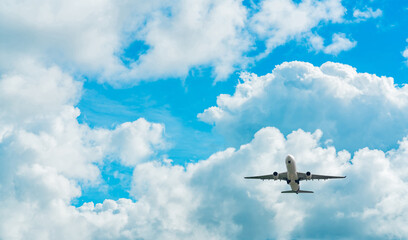 Fototapeta Commercial airline flying on blue sky and white fluffy clouds. Under view of airplane flying. Passenger plane after take off or going to landing flight. Vacation travel abroad. Air transportation. obraz