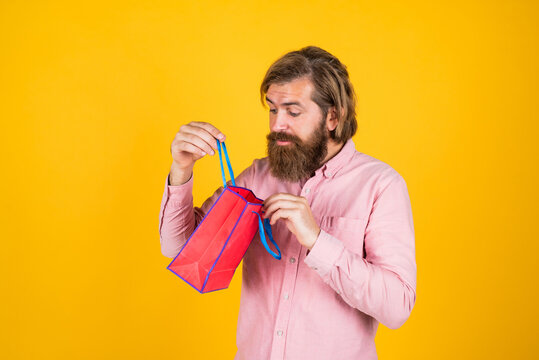 just look here. surprised bearded man holding gift package. happy birthday or anniversary. holiday celebration. surprise for him. shopping and sale. mature brutal hipster with present. buy in mall