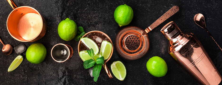 Moscow Mule. Preparation cocktail  with ginger beer, vodka, lime and ice. Copper bar tools. Black bar counter. Top view
