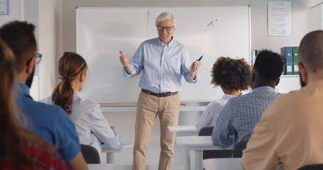 Obraz Senior male teacher with a group of students teaching in classroom. - fototapety do salonu