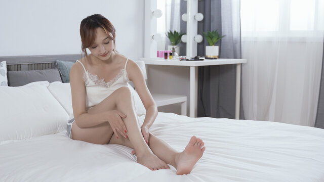 full length happy charming girl in white skimpy wear is putting lotion on her lower limb in the bedroom. beauty, health and daily skincare routine concept. real moments.