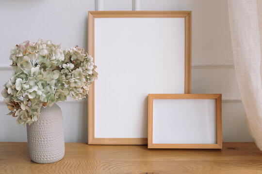 Blank white empty picture frames mockup and modern ceramic vase with dry hydrangea on wooden table. White wall background. Scandinavian interior.