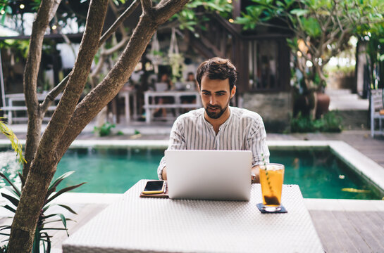 Young bearded man working on laptop