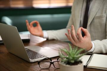 Obraz Businessman meditating at desk in office, closeup - fototapety do salonu