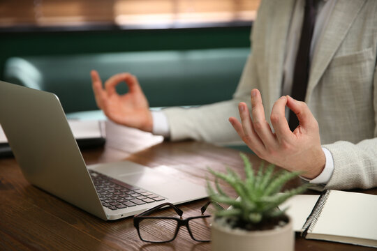 Businessman meditating at desk in office, closeup