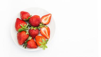 Obraz Czerwone, dojrzałe truskawki na białym tle, na talerzu - fototapety do salonu