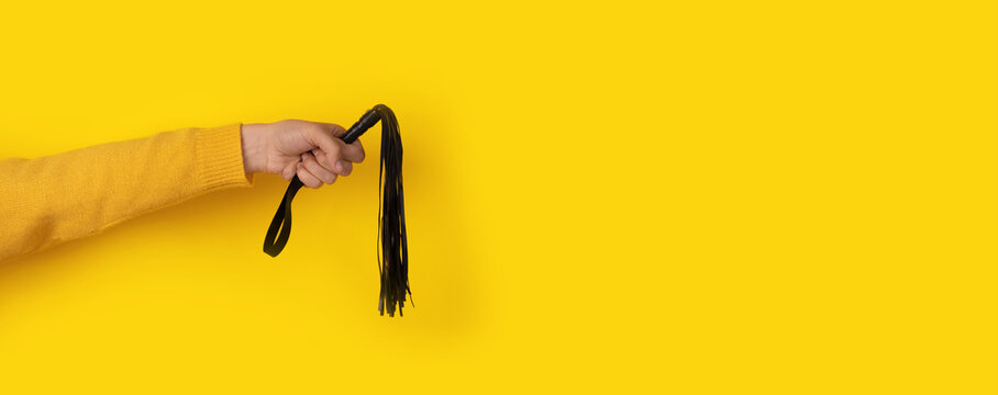 leather whip in hand over yellow background, BDSM accessories, panoramic layout