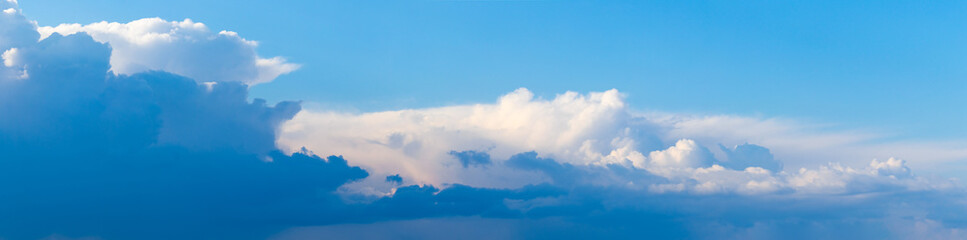Panorama of blue sky with dark and light clouds