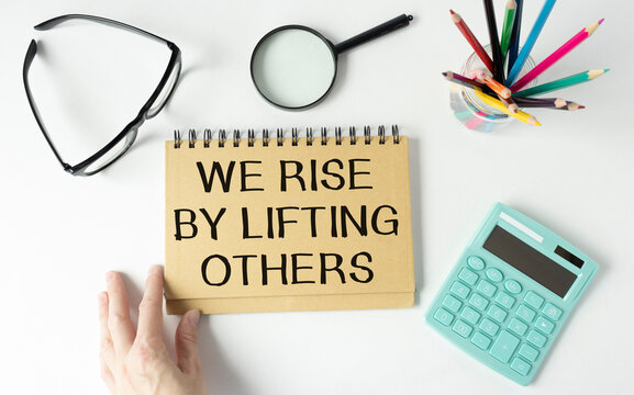 Inspirational and motivation life quote on notepad - We Rise by Lifting Others.
