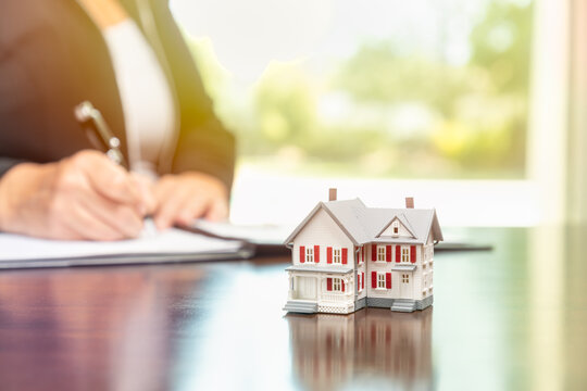 Woman signing real estate contract papers with small model home in front.