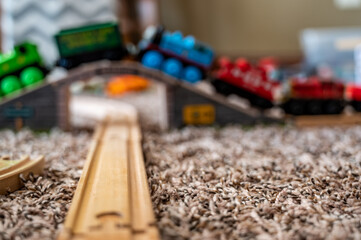 selective focus on wooden toy train track with blurred bridge and locomotive in background
