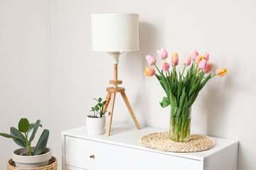 Obraz Bouquet of tulip flowers on chest of drawers near white wall - fototapety do salonu