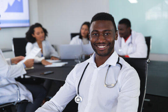 Portrait of african american male doctor smiling while sitting on a chair in meeting room