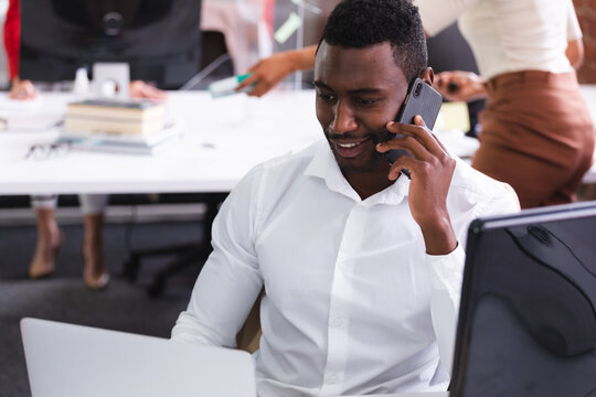 African american man talking on smartphone while sitting on his desk at modern office