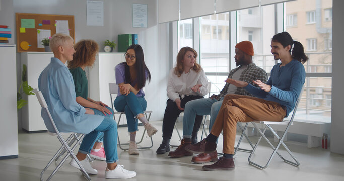 Diverse people talking and helping each other in therapy session or support group meeting