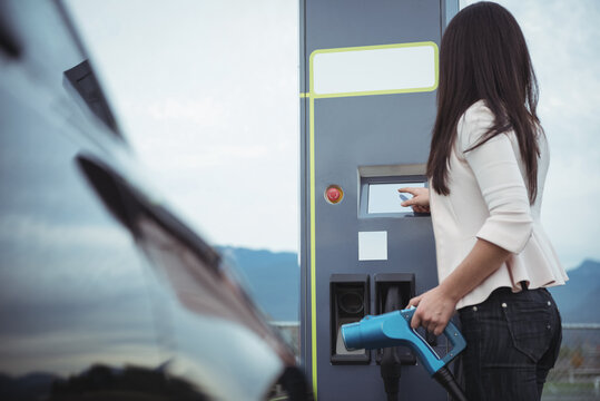 Caucasian woman holding charging cable for electric car keying in code in charging station