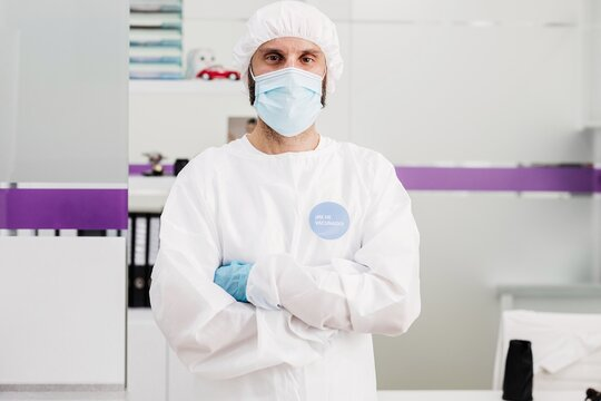 Positive male doctor with latex gloves and protective medical mask with I'm vaccinated message sticker on white uniform standing with arms crossed in modern medical office and looking at camera
