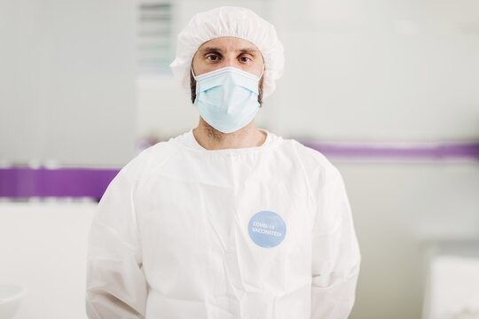 Positive male doctor with latex gloves and protective medical mask with covid-19 vaccinated message sticker on white uniform standing in modern medical office and looking at camera