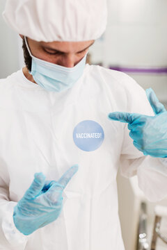 Positive male doctor with latex gloves and protective medical mask pointing at I'm vaccinated message sticker on white uniform standing in modern medical office