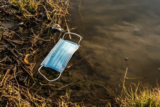 From above of plastic medical mask floating on water of pond showing concept of environmental pollution with plastic