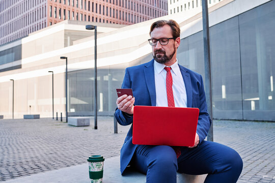 Concentrated male entrepreneur sitting on street with laptop and making payment with plastic card during online shopping
