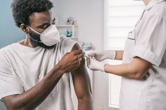 Cropped unrecognizable female medical specialist in protective uniform, latex gloves and face mask vaccinating African American man patient in clinic during coronavirus outbreak