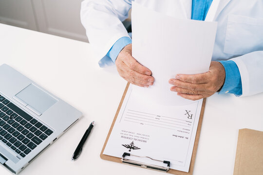 Top view of crop unrecognizable male doctor working at table with paper form and netbook against stethoscope in hospital