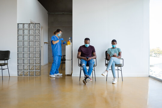 Young African American female and male patients browsing on smartphone while sitting in a waiting room near female doctor in protective uniform, latex gloves and face mask before vaccinating in clinic during coronavirus outbreak
