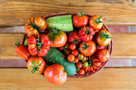 Top view of a tray full of tomatoes and cucumbers on the wooden table