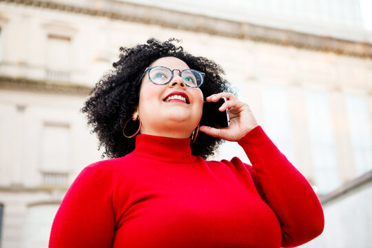 From below of content overweight female in red clothes and eyeglasses talking on cellphone while looking up in city
