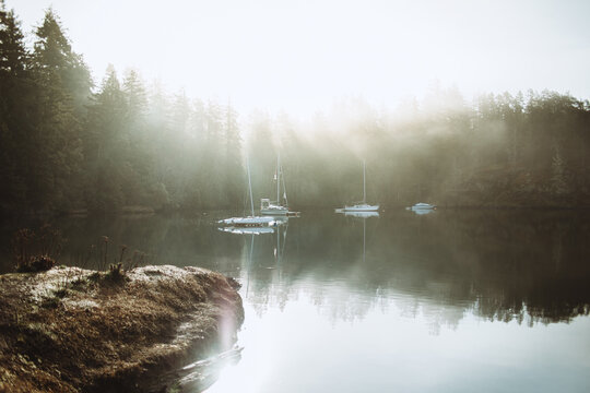 Nice landscape of a lake with some boats on a foggy day