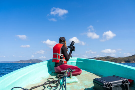 Back view of anonymous female traveler in life jacket and cap with a professional camera during trip