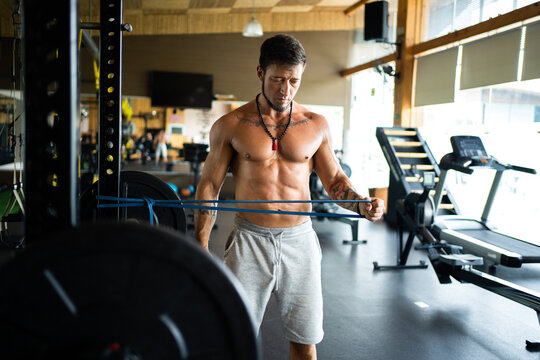 Focused sportsman with naked torso exercising with elastic band while pumping arms during workout in fitness center