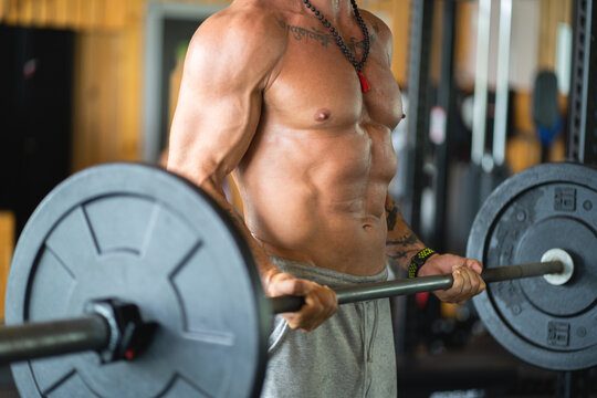 Cropped unrecognizable strong male athlete lifting heavy barbell while shouting during workout in gym